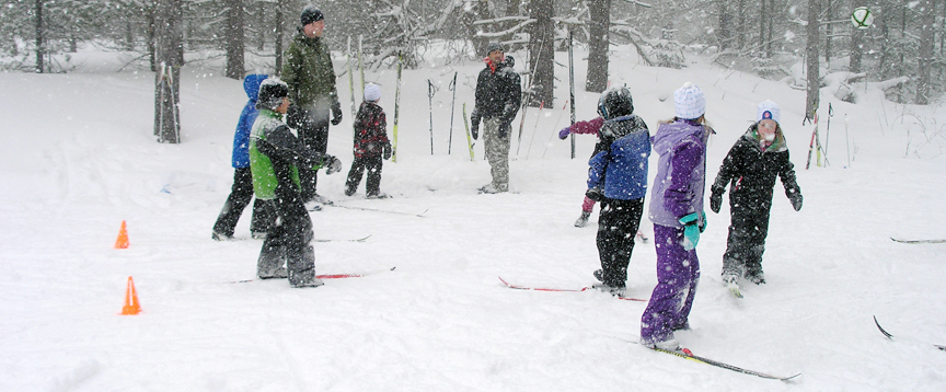 Children learning to ski on a snowy day